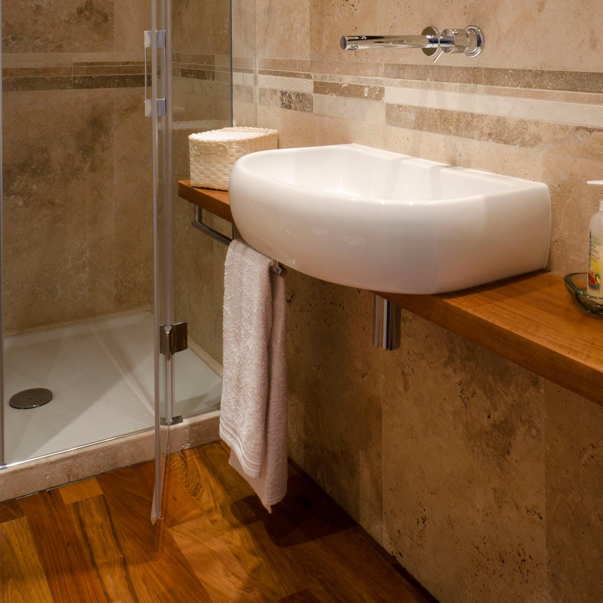 Bagno con rivestimento in travertino e pavimento in legno - Pietre ...