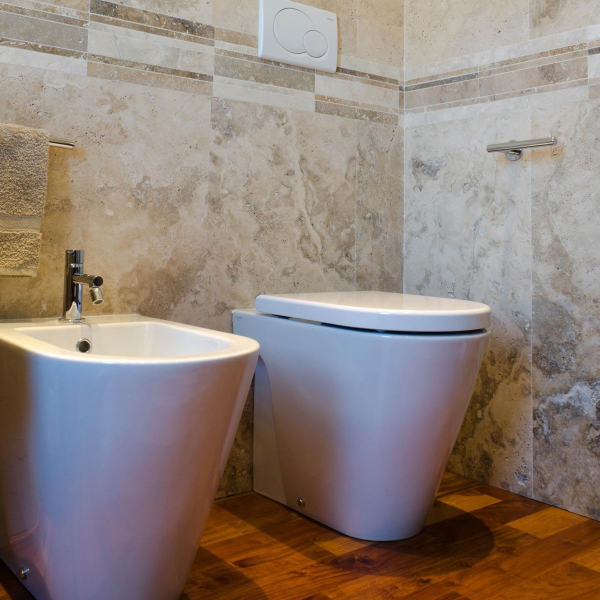 Bagno con rivestimento in travertino e pavimento in legno ...