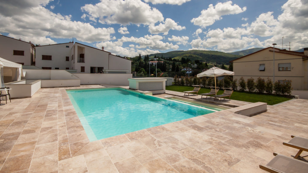 Esterno piscina in travertino Leather Brown in un resort in campagna