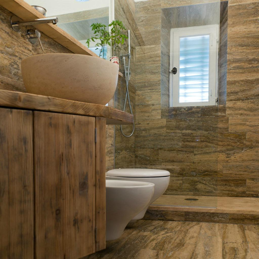 Bagno in travertino con lavabo da appoggio, rivestimenti e piatto doccia