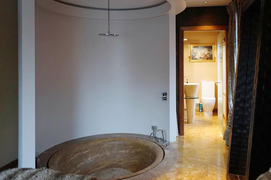 Doccia con vasca circolare in travertino scuro bagno padronale residenza dublino