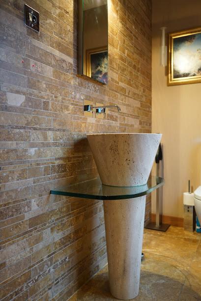 Lavabo cono freestanding e parete con rivestimenti in mosaico