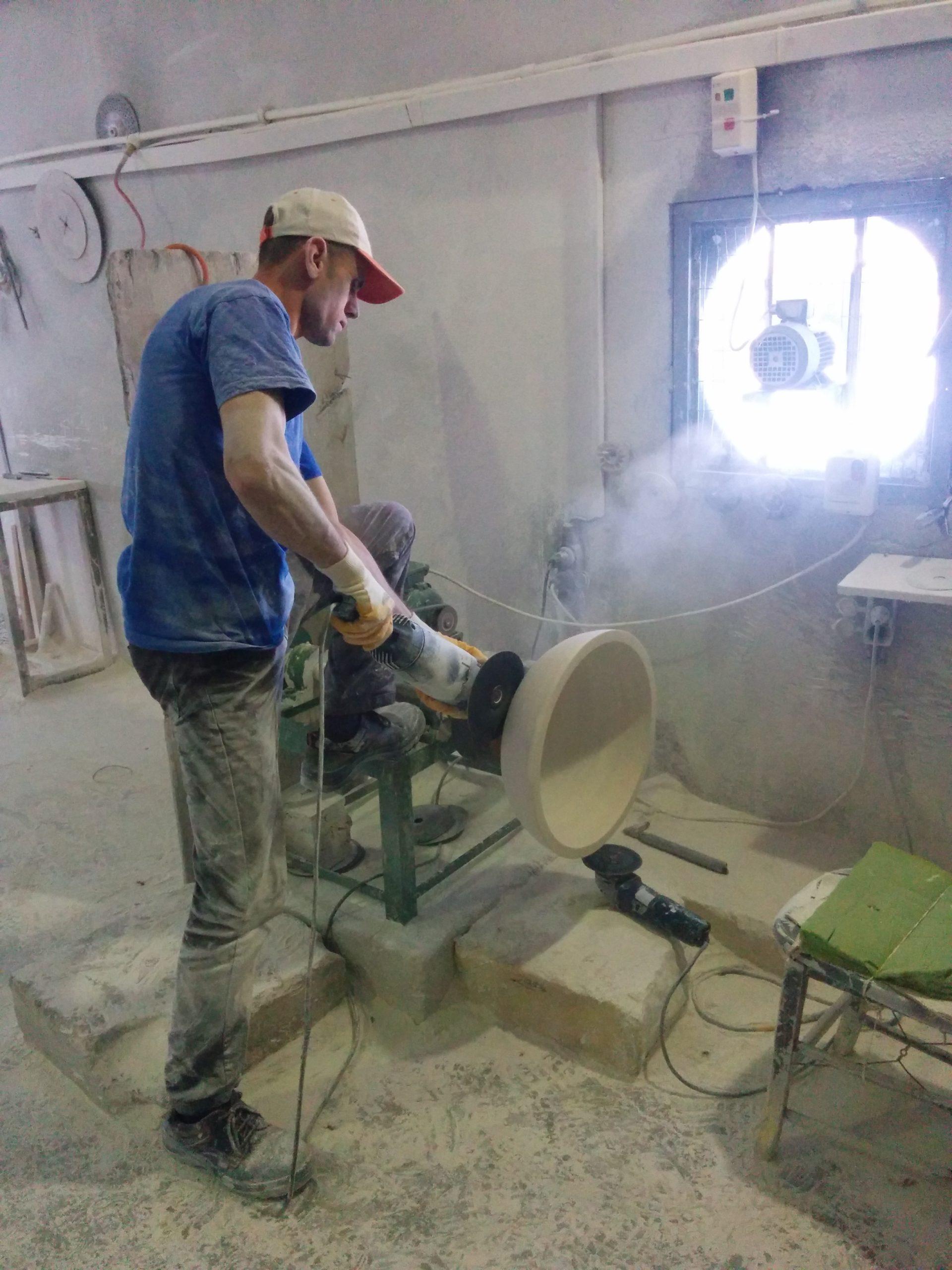 Rifinitura esterna al tornio di un lavabo in massello di Travertino